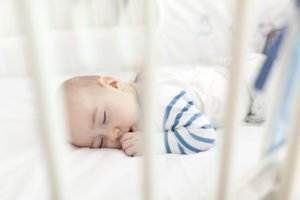 A small child takes a nap in a white blanketed crib