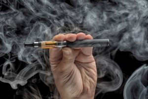 hand-holding-an-electronic-cigarette-over-a-dark-background-000060764156_medium
